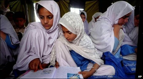 Pakistani female students walk by their make-shift classroom set up in a tent in Kanju in Pakistan's Swat valley, April 26, 2010.