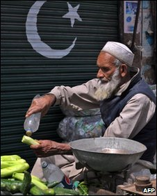 An elderly Pakistani vendor washes a cucumber at his roadside stall in Mingora, the capital of Swat valley on March 25, 2010.