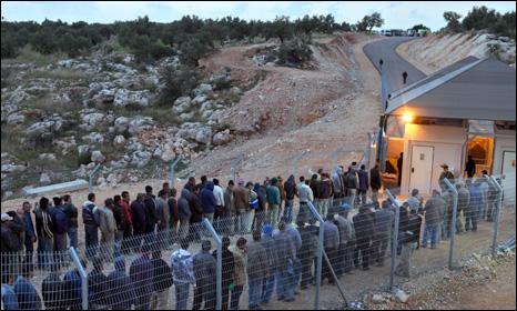 Palerstinian labourers queue up  to cross an Israeli checkpoint in the West Bank on their way home from work (picture from January 2010)