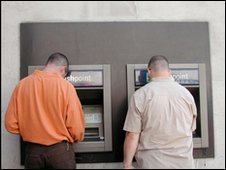 Two men at ATMs.