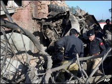 Police officers examine the wreckage of vehicles at the site of the blast