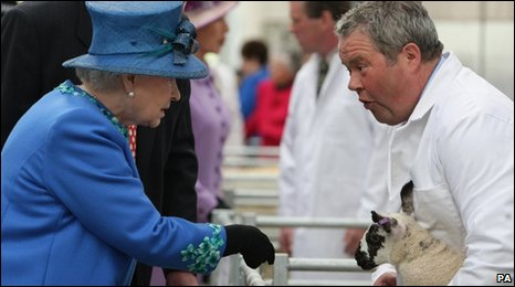 The Queen meets farmer Gwyn Price and one of his lambs during her visit to Welshpool Livestock Market, Powys