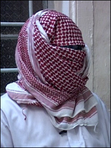 A torture victim, wrapped in a scarf to cover his face