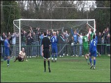 Guernsey footballers and crowd celebrate Ross Allen's 91st minute goal