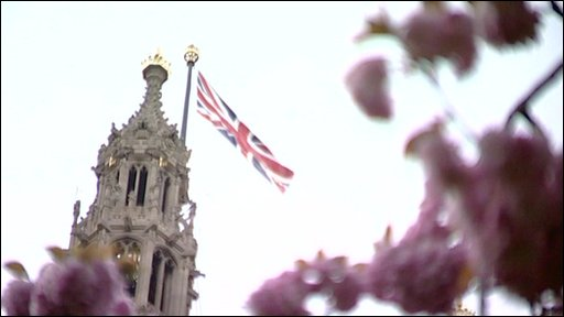 Union flag flying on tower at Westminster, seen from behind blossoming trees