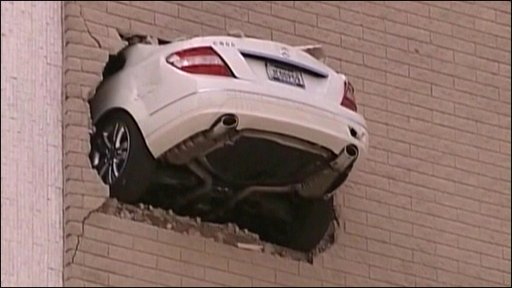 The car dangles through a wall