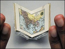 Staff member Radhika Dandeniya views the world's smallest atlas ever to be published which was commissioned for the dolls' house of Queen Mary consort to George V