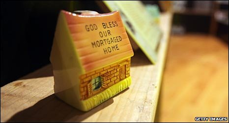 """Recession art - ceramic house with """"God Bless This Mortgaged House"""" painted on roof"""