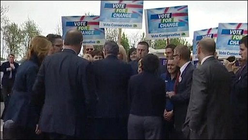 Tory supporters wave placards outside a labour campaign event