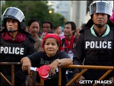 A protester stands next to police in Bangkok on 2 May 2010