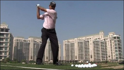 A man takes a golf swing