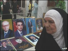 A woman walks past pictures of killed Iraqi journalists during a gathering at the Iraqi Syndicate of Journalists to mark World Press Freedom Day in Baghdad , May 2010