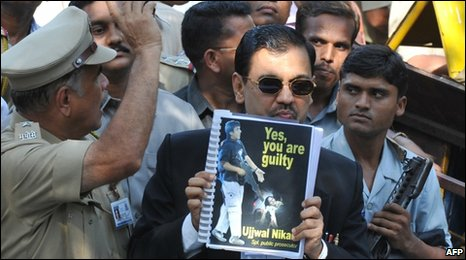 Special public prosecutor Ujjwal Nikam shows a copy of the verdict to the media outside the prison, where the Mumbai attacks trial is being held