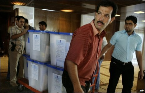 Electoral workers transport ballot boxes to a recount