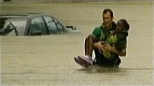 A man carries a child through flood water in Nashville, Tennessee