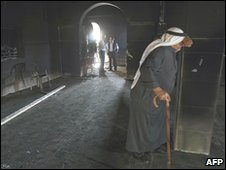 A Palestinian man inside a burnt mosque in the West Bank village of Lubban al-Sharqiya, south of Nablus on May 04, 2010