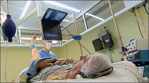 James McLaren watches a DVD during surgery