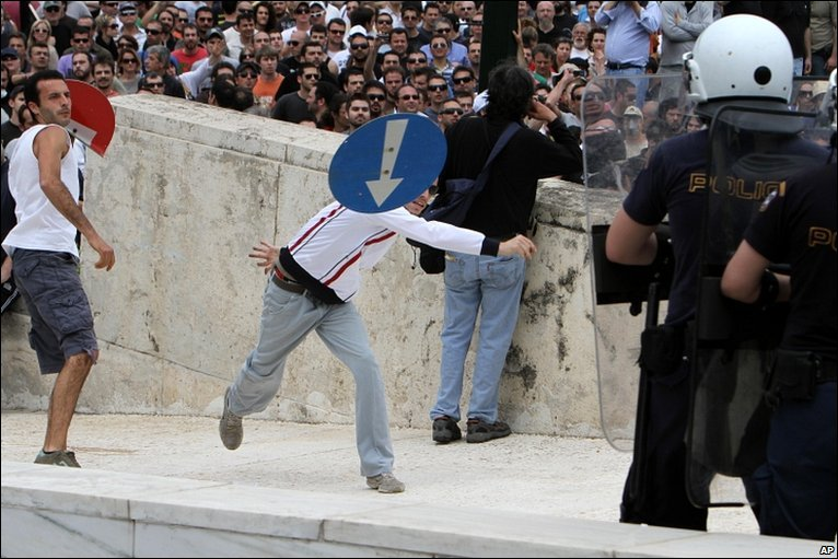 A protester throws a traffic sign at riot police in front of Greece's parliament building in Athens, 5 May, 2010