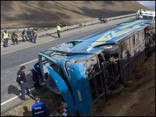Towing company employees inspect the wreckage of the bus after its accident near Cape Town on 5 May 2010