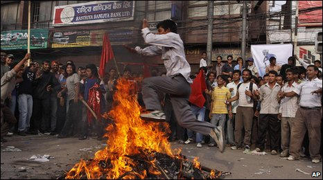 "A supporter of the Communist Party of Nepal (Maoist) jumps over a  burning effigy of Nepal""s prime minister as they block a road in  Katmandu"