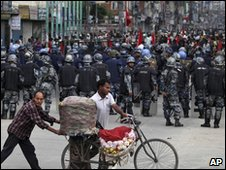 Nepalese transport fruits on a bicycle as they walk past Nepalese  policemen near a barricade in Katmandu, Nepal