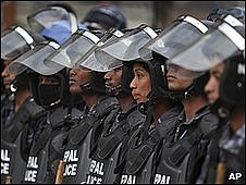 Nepalese police in riot gear stand guard near a barricade in  Katmandu