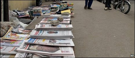 Pedestrians walk past newspapers announcing the death of Nigerian President Umaru Yar'Adua, on Ikoyi Island in Lagos