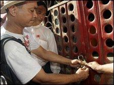 NLD member locks the gates to the Rangoon headquarters on 6 May 2010