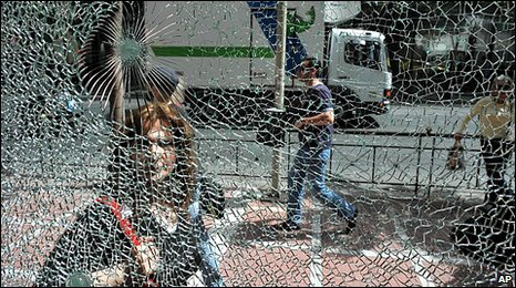 Pedestrian walks past broken window in Athens