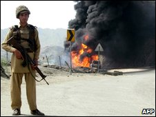 Pakistani soldier beside burning truck