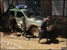 Afghan children walk through mud in Herat province on May 5, 2010