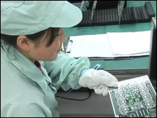 A ZTE employee assembles mobile phone components