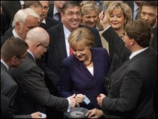 Angela Merkel, centre, waits to cast her ballot in the Bundestag, Berlin, 7 May 2010