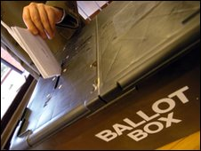 A vote being cast into a ballot box