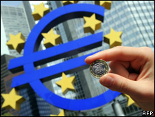 Woman holds a euro coin in front of the symbol of the euro (file)