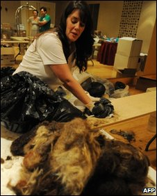A New Orleans hotel worker prepares human hair to be stuffed into nylon stockings