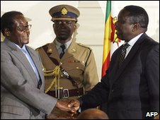 Robert Mugabe (L) and Morgan Tsvangirai shake hands in Harare - 21 July 2008