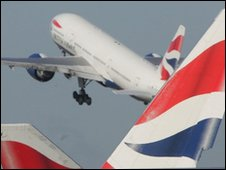 BA aircraft takes off behind a number of British Airways tail fins