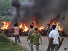 Naga civilians block a road in Manipur protest against the state government's decision to ban the entry of Mr Muivah on 7 May 2010