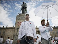 Robinson Devia (centre) is chained to Simon Bolivar's statue. Photo: 10 May 2010