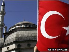 A woman waves a Turkey flag in front of a mosque in Istanbul, Turkey.