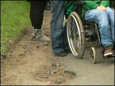 Wheelchair on potholed road