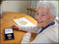 Pat Dunstan holding an award for her Great Uncle