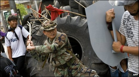 Khattiya Sawasdipol tests a red-shirt guard's shield in Bangkok, 11 May