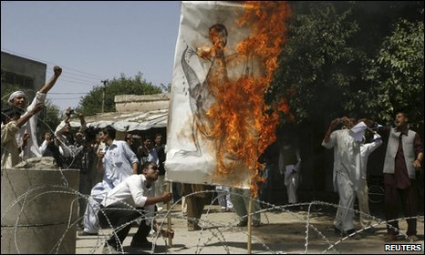 Afghan men burn a painting of Iranian President Mahmood Ahmedinejad during a protest outside the Iranian Consulate in Jalalabad