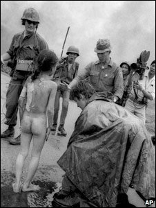Kim Phuc is surrounded by Television crews and South Vietnamese troops following the napalm attack 