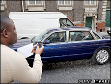 A man using a mobile phone to take a photograph of Prime Minister David Cameron in a car