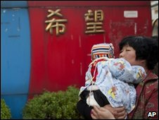 A woman holds a baby near the gate of Zhongxin Kindergarten, file pic