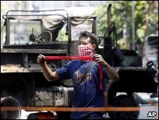 An anti-government protester next to the wreckage of an army truck in Bangkok, 15 May