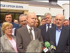 Sir Reg Empey (centre) tells the media he is standing down